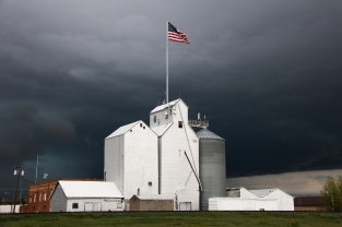 White grain elevators contrast brightly against a dark sky